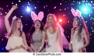 Girls at bachelorette party having fun dancing, throws glitter confetti