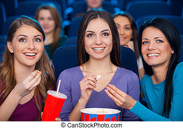 Girls at the cinema. Happy young women eating popcorn and drinking soda while watching movie at the cinema together