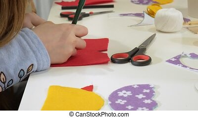 Girls at the lesson with the teacher sew a soft toy with...