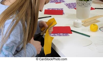 Girls at the lesson with the teacher sew a soft toy with their own hands