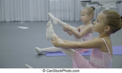 Girls ballerina sit on mat and pull up one leg for...