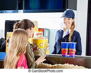 Girls Buying Snacks From Female Seller At Concession Stand