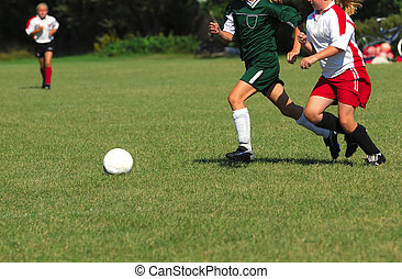 Two girls chase a soccer ball across a grass field.