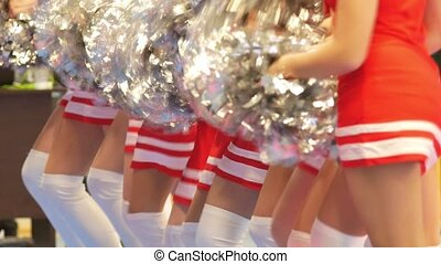 Girls cheerleaders in a red dresses dancing with pompoms,...