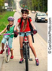 Girls children cycling near city road. - Bikes bicyclist ...