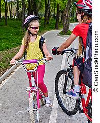 Girls children cycling on spring yellow bike lane. - Bikes ...