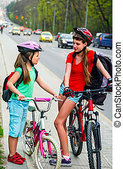 Girls children cycling on yellow bike lane. There are cars ...