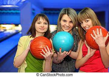 Girls closely stand alongside, hold balls for bowling and...