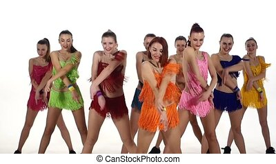 Girls dancing synchronously in colorful dresses over white background. slow motion