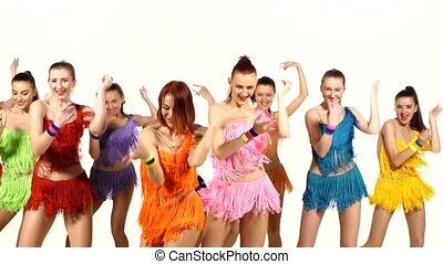 Girls dancing synchronously in colorful dresses over white...