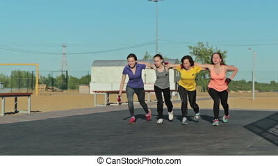 Girls do fitness exercise steps together, outdoor