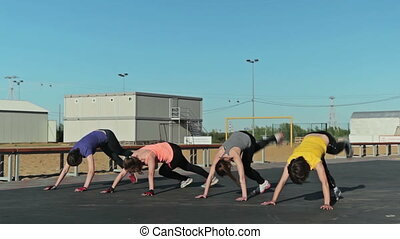 Girls doing burpee exercise, and another exercise