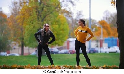 Girls doing gymnastics in the park. Autumn. Fall season....