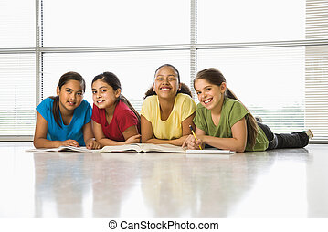 Preteen girls of mutiple ethnicities sitting together on floor with schoolwork smiling at viewer.