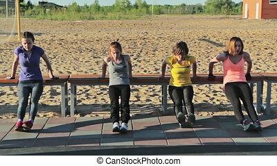Girls doing push-ups on bench in park