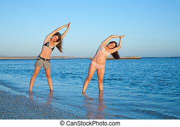 girls doing yoga against sea