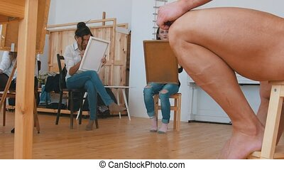 Girls draws a muscular shirtless guy on a canvas, sitting...