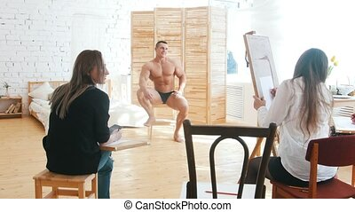 Girls draws a muscular shirtless guy on a canvas, they're...