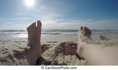 Girls feet in the sand of the sea.