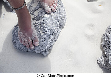 Girl\'s Feet Standing On Beach Rock