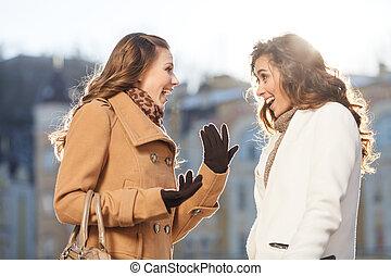 Girls gossiping. Two beautiful young women gossiping while...
