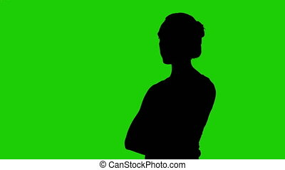 Girl's half turned silhouette with arms crossed on green background