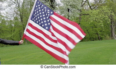 Girl's hand holding a flag of the US