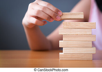 Girl's hand stacking wooden blocks.