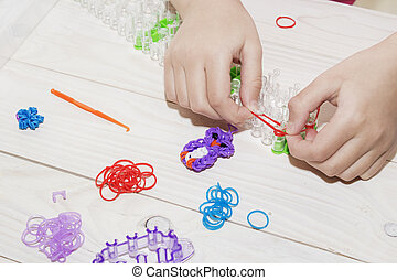 Girl's hand with wristbands and rings made of rubber bands