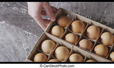 Girl's hands are taking a fresh eggs from paper tray, on a...
