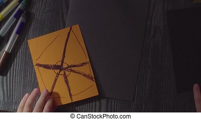 Girl's hands drawing spider web on a card. Preparing for the celebration of Halloween