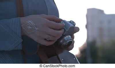 Girl's hands hold the vintage old film camera. Girl camera shutter clicks close up