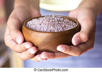 Girl's hands holding lavender bath salt in a wooden bowl