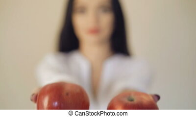 Girl's hands holds two big red apples in front of camera, blurred background 4K