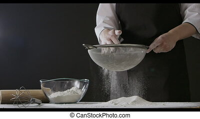 Girl's hands take white flour from glass bowl and sieve from sifter on a wooden table. Slow motion, Full HD video, 240fps, 1080p. Process preparing of homemade pastry.