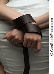 Girls hands tied up with a leather belt close up view