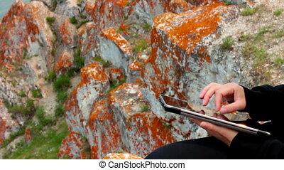 Girl's hands using a tablet PC on the rock, Olkhon Island,...