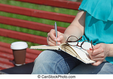 girls hands with pen writing on notebook in park