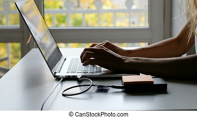 girls hands working with laptop near window