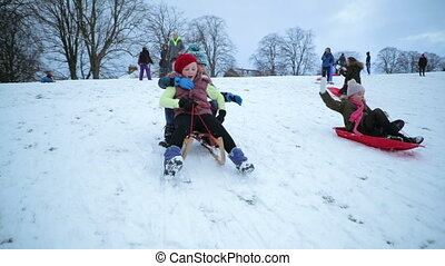 Girls Having a Sled Race - Little girls are being pushed ...
