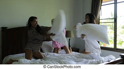 Girls Having Fun Pillow Fight In Bedroom, Young Cheerful Women Friends Happy Laughing