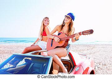 girls having fun playing guitar on th beach in a car