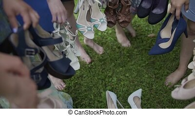 Girls holding sandals in their hands, smiling and joking