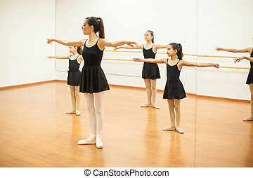 Girls imitating teacher in a dance class - Group of girls in...