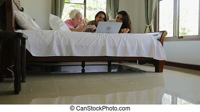 Girls In Bedroom Using Laptop Computer Lying On Bed Talking,...