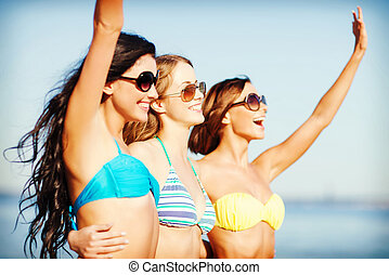girls in bikini walking on the beach - summer holidays and...