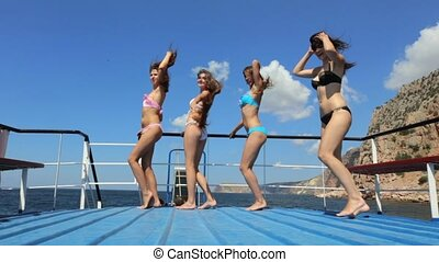 Girls in bikinis dancing on the pleasure boat that is in the sea