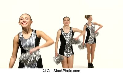 Girls in black costume  with pom-poms dancing on cheerleading competitions, smiling at the camera