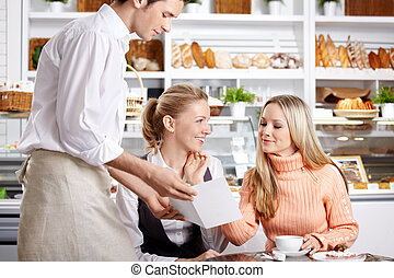 Girls in cafe - Young girls do the order to the waiter in...