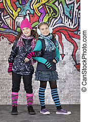 Girls in front of the wall covered with graffiti